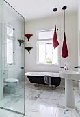 Modern, elegant bathroom with marble floor and vintage free-standing bathtub below window