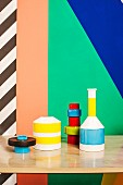 Colourful graphic pattern on wall behind still-life arrangement of vases