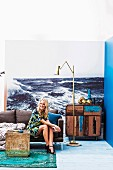 Young woman sitting in front of photo mural of the sea in eclectic maritime interior