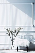 Wall with decorative strips, in front of it stool with white fur cover and branches in a glass vase