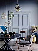 Pendant lamps with diamond-shaped wire lampshades above round table and retro chairs
