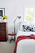 Vintage chest of drawers and standard lamps in bright, vintage-style bedroom with carpet in period apartment