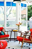 Classic retro furniture in orange in window bay with garden view