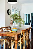 Holztisch mit rustikalen Bistrostühlen auf Edelholzparkett in restauriertem Altbauambiente