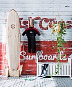 Maritime wall decoration - wetsuit hung from hook, surfboard and white wooden bench