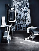 Console table, metal clothes rail and and wall covered in stylish black and white photos in open-plan dressing room