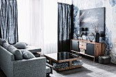 Grey mottled couch, walnut table with lower shelf and sideboard against wall