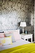 Weisses Bett mit gelbem Überwurf und Pastell Kissen vor gemusterter Tapetenwand mit Pfauenmotiv in Grautönen