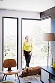 Woman wearing yellow top and dog in front of frameless corner window, replica of classic chairs and postmodern standard lamp with plexiglas base
