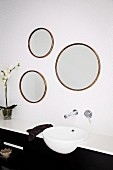 Trio of mirrors made from old round picture frames above modern sink with taps mounted on white mosaic wall tiles