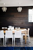 Stacking chairs, large wooden table, crystal chandelier, dark wooden wall and royal blue rug on travertine floor in dining room