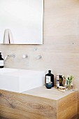 Elegant wooden washstand with white sink against wood-clad wall