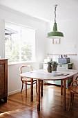 Ausziehbarer Holzesstisch mit Holzstühlen und grüner Retro-Pendelleuchte, Vintage Kommode und glänzendem Parkettboden
