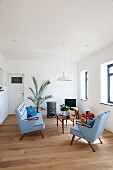 50s-style sofa set with pale blue upholstery and delicate wooden coffee table on wooden floor in minimalist interior