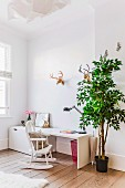 White desk, vintage rocking chair, green tree and faux hunting trophies in bright child's bedroom
