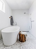 Accessible shower area, free-standing bathtub and rustic wooden stool in designer bathroom