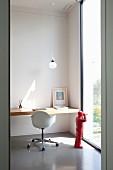 Eingespannte Schreibtischplatte aus Holz und Retro Drehstuhl mit Sitzschale neben raumhohem Fenster