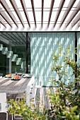 Holzterrasse unter Pergola mit Lamellenabdeckung, vor modernem Wohnhaus mit Licht-Schattenspiel auf Glasfassade
