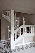 Staircase with carved balustrade and mosaic hall floor