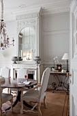 Hell bezogene Stühle im Rokoko Stil um Esstisch, im Hintergrund offener Kamin und eingebauter Spiegel in geschnitzem Wandpaneel