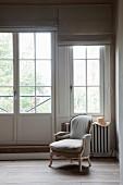 Armlehnsessel im Rokoko Stil vor Fenster in traditionellem Ambiente