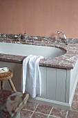 Badewanne mit Marmor Einfassung und hellgrau lackierte Holzfront