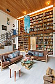 Sofas and side table in front of double-height bookcases with airy steel and wood gallery