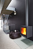 Fire in cast iron log burner on black wall in contemporary stairwell with staircase in background