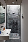 Sink with wall-mounted tap and floor-level shower area with slate-tiled walls in narrow modern bathroom