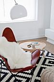 Butterfly Chair und Tabletttisch auf grafisch gemustertem schwarz- weißem Teppich