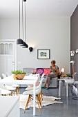 Moderner Esstisch mit Klassiker Schalenstühlen, Frau auf Sofa im Hintergrund