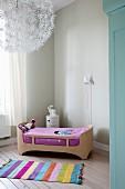 Gestreifter Teppich vor Designer-Kinderbett, restaurierter Dielenboden und Blütenleuchte an der Decke