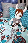 Fantasy figure soft toy on blue and brown, patterned bed linen and retro-patterned pillows in cot