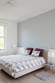 Double bed with pastel bed linen, grey-painted wall above white base element in minimalist bedroom