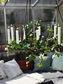 White lit candles in chandelier wound with ivy