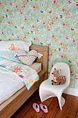 Kinderbett aus Holz vor Blümchentapete, Panton-Kinderstuhl mit Plüschtier