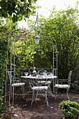Filigrane Metallstühle und Tisch unter pavillonartiger Pergola aus Metall in idyllischem Garten
