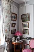 Runder Beistelltisch im Rokoko Stil in Zimmerecke, oberhalb an Wand aufgehängte Bilder