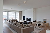 Elegant, minimalist urban apartment with beige sofa combination, open fireplace and low custom sideboard