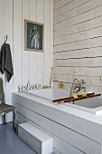 Built-in bathtub with white wood-clad surround and walls