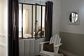 White-painted wooden armchair in corner next to interior window with view into bedroom