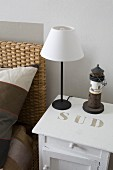 Minimalist table lamps with white lampshade on white-painted bedside cabinet with stencilled lettering