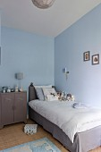 Single bed with grey valance and white bed linen next to retro metal cabinet in child's bedroom with pale blue walls