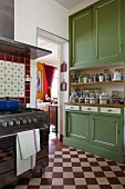 Red and white chequered floor, green dresser and gas cooker in traditional cooker