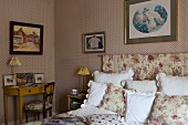 Classic wallpaper, rose-patterned textiles and antique furniture in traditional bedroom