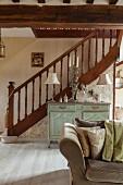 Gedrechseltes Treppengeländer in offenem, renoviertem Wohnraum mit antiker Kommode und elegantem Flair