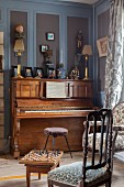 Piano against grey and blue wood panelling in elegant parlour