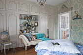 Elegant fitted wardrobes with open-fronted shelving modules and chaise longue in antique-style bedroom