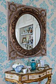 Antique mirror above gilt console table on ornate wallpaper