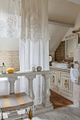 White curtains and wooden balustrade in antique ensuite bathroom